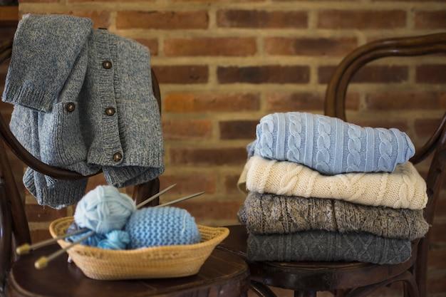 Przędza i ciepłe ubrania na krzesłach