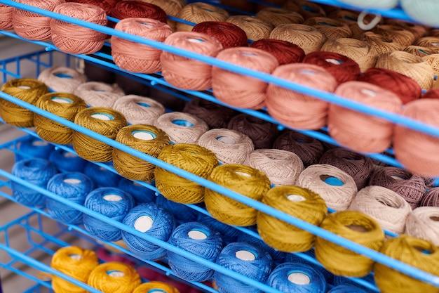 Przędza lub kłębki wełny na półkach w sklepie do robienia na drutach i robótek ręcznych
