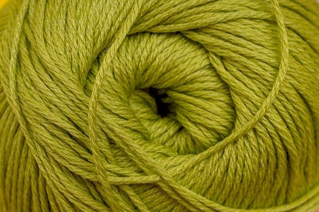 Przędza na drutach zbliżenie zielone tło.