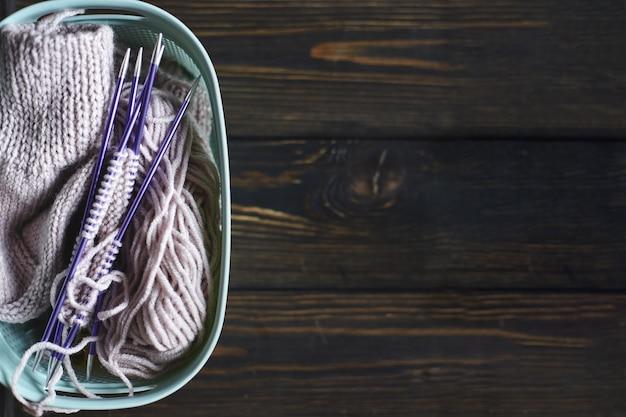 Przędza w cewkach i drutach na drewnianym stole. domowe hobby. ręcznie robione skarpety z igłami i kulką z przędzy