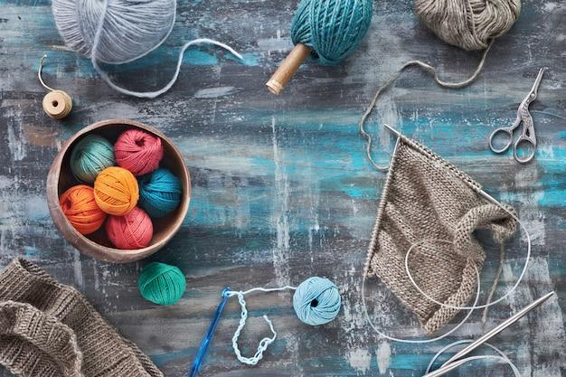 Przędza wełniana i iglice, kreatywne tło dziewiarskie w niebieskich turkusowych kolorach