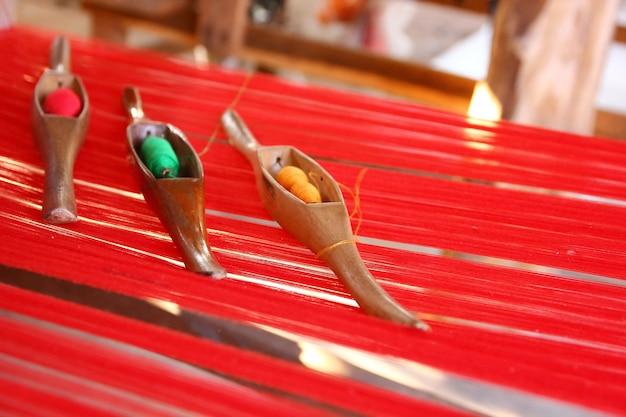 Przędza z drewna wahadłowego z czerwonymi przędzami na lokalnym krośnie tkackim, abstrakcyjne tło.