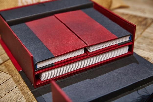 Przedziały czerwonego i czarnego pudełka odsłaniają czasopisma o różnej wielkości