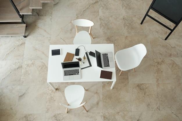 Przegląd białego stołu z krzesłami i gadżetami na nim