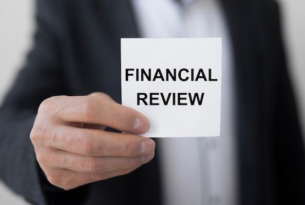 Przegląd finansowy napis na papierze w ręku biznesmena
