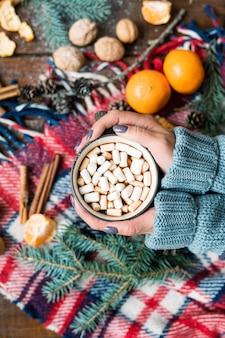 Przegląd kobiecych rąk trzymających kubek gorącego napoju z piankami na ciepłym szaliku w kratkę