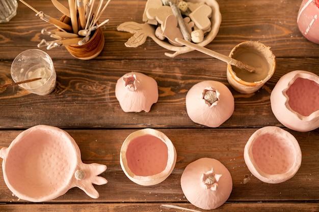 Przegląd kreatywnych przedmiotów z gliny, takich jak granat, pędzle i kilka narzędzi ręcznych w szklankach na drewnianym stole