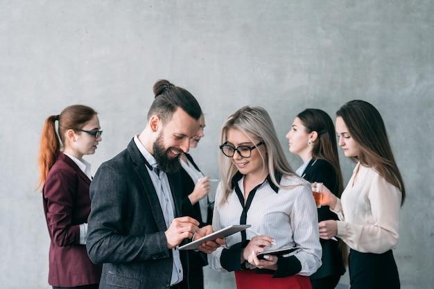 Przegląd opinii. młody biznesmen przeglądanie tabletu podając instrukcje do sekretarza.