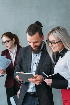 Przegląd opinii. rozwój biznesu. młody uśmiechnięty lider zespołu, który przegląda tablet, podając wskazówki do sekretarki.
