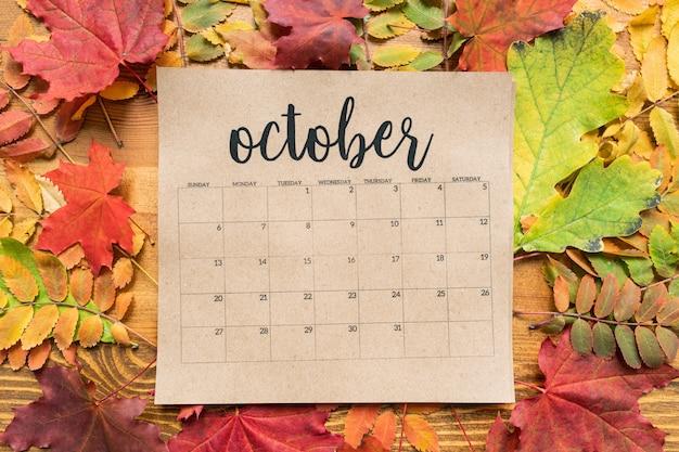 Przegląd październikowego kalendarza i grupy kolorowych liści jesienią na drewnianym stole