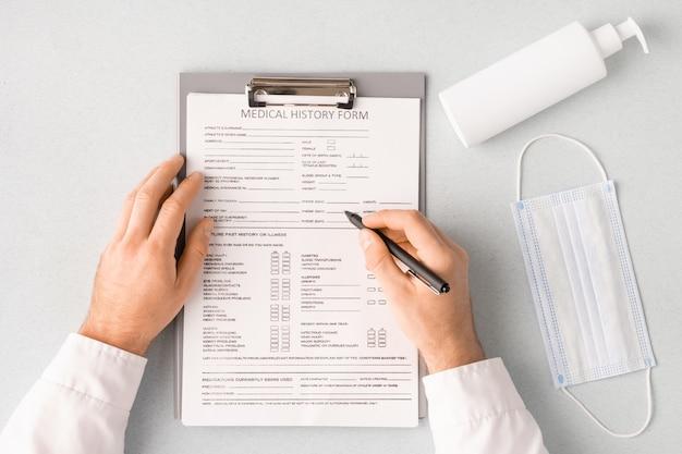 Przegląd rąk lekarza długopisem nad formularzem historii choroby, wypełniając dane osobowe za pomocą maski i środka odkażającego po prawej stronie