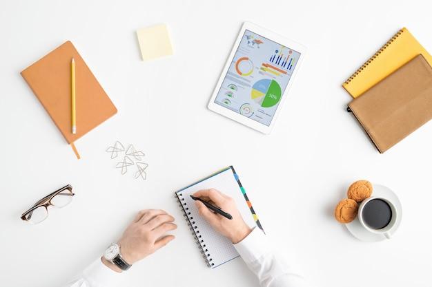 Przegląd rąk młodego biznesmena trzymając pióro na pustej stronie notesu
