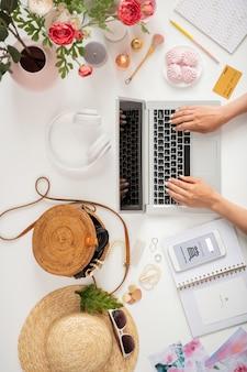 Przegląd rąk młodej kobiety lub bizneswoman na klawiaturze laptopa w otoczeniu różnych obiektów