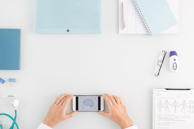 Przegląd rąk pracownika medycznego trzymających smartfon z informacjami o ludzkim mózgu na ekranie otoczonym innymi materiałami