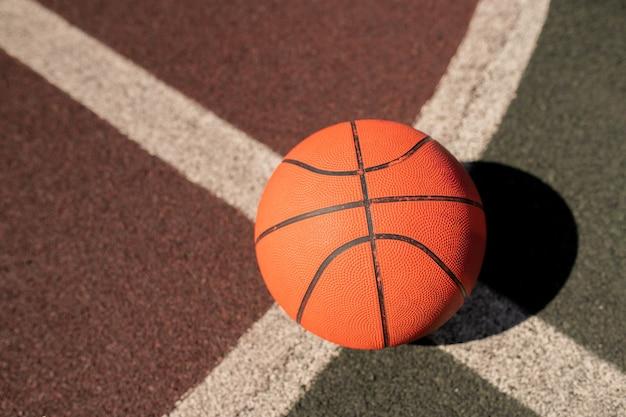 Przegląd sprzętu do koszykówki na skrzyżowaniu dwóch białych linii na stadionie lub boisku do gry