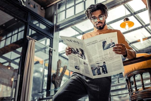 Przegląd wiadomości. zadowolony międzynarodowy mężczyzna w okularach, wpatrując się w gazetę