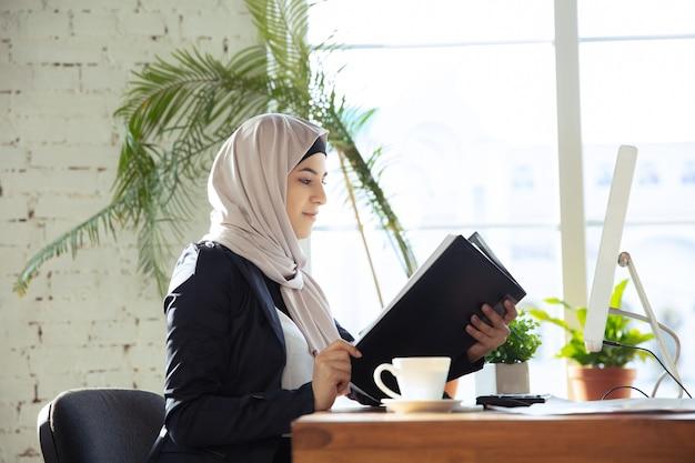 Przeglądanie dokumentów. portret pięknej arabskiej bizneswoman noszącej hidżab podczas pracy na openspace lub w biurze. pojęcie zawodu, wolność w biznesie, sukces, nowoczesne rozwiązanie.