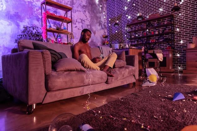 Przeglądanie haniebnych zdjęć. ciekawy nagi afroamerykanin trzymający smartfon otoczony dekoracjami i śmieciami