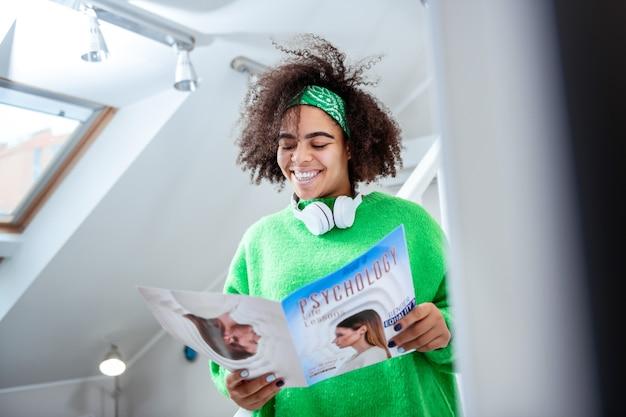 Przeglądanie podręcznika. śmiejąca się pani we wszystkich zielonych obserwujących informacjach przedstawionych w podręczniku podczas przygotowań