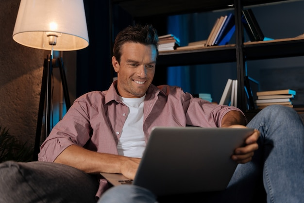 Przeglądanie witryn. przystojny, ambitny, beztroski facet siedzi na kanapie