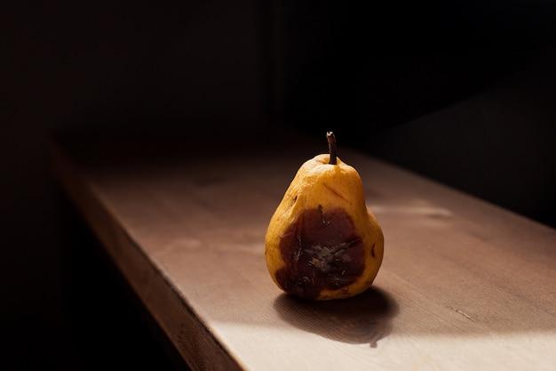 Przegniła żółta bonkreta na drewnianym stole