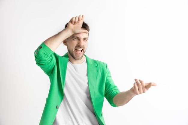 Przegrani wracają do domu. portret szczęśliwy facet pokazujący przegrany znak na czole i uśmiechnięty z powodu zwycięstwa i śmiejący się na szarym tle