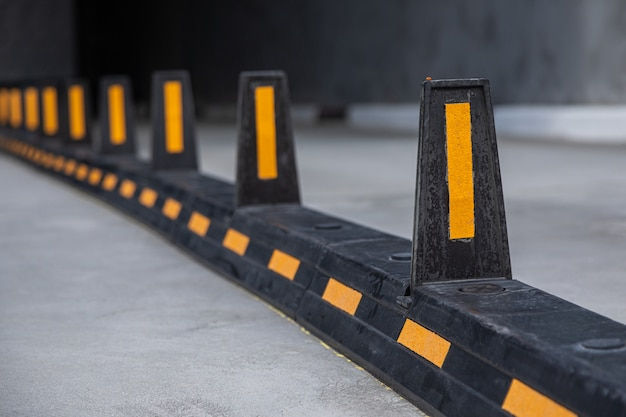 Przegrody drogowe z żółtymi paskami na drodze do garażu podziemnego