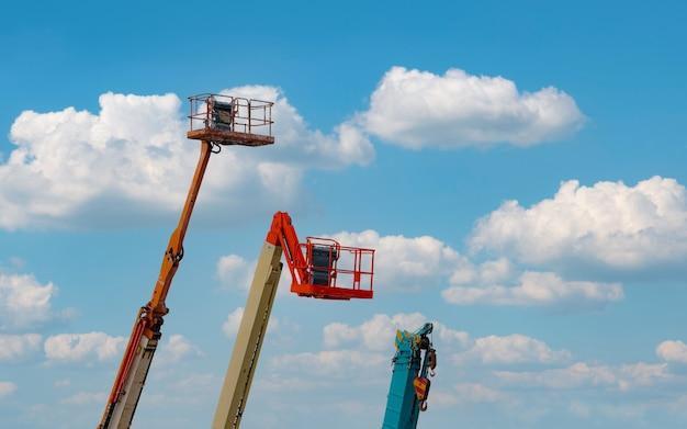 Przegubowy podnośnik wysięgnika. podnośnik koszowy. podnośnik teleskopowy na tle błękitnego nieba. wynajmę i sprzedam mobilny dźwig budowlany. konserwacja i naprawa hydraulicznego podnośnika wysięgnika. dealerzy dźwigów.