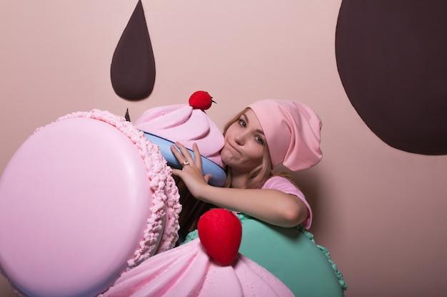 Przejadająca się blond kobieta w różowej czapce i koszulce, bawiąca się dużymi makaronikami i babeczkami w studio