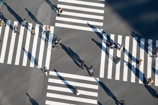 Przejeżdżaj Przez Skrzyżowanie W Tokio, Japonia, Gdzie Ludzie Przychodzą I Odchodzą Premium Zdjęcia