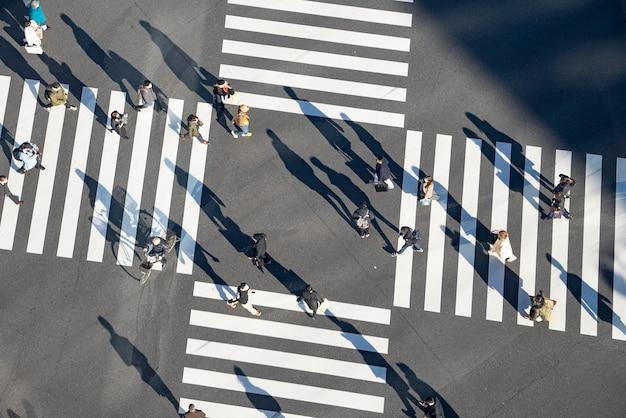 Przejeżdżaj przez skrzyżowanie w tokio, japonia, gdzie ludzie przychodzą i odchodzą