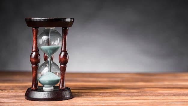 Przejrzysty piaska hourglass na drewnianym biurku przeciw popielatemu tłu