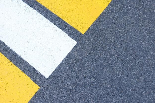 Przejście dla pieszych z żółtobiałymi paskami na nawierzchni drogi