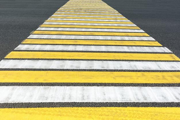 Przejście dla pieszych z żółtymi i białymi paskami oznakowanie skrzyżowania jezdni