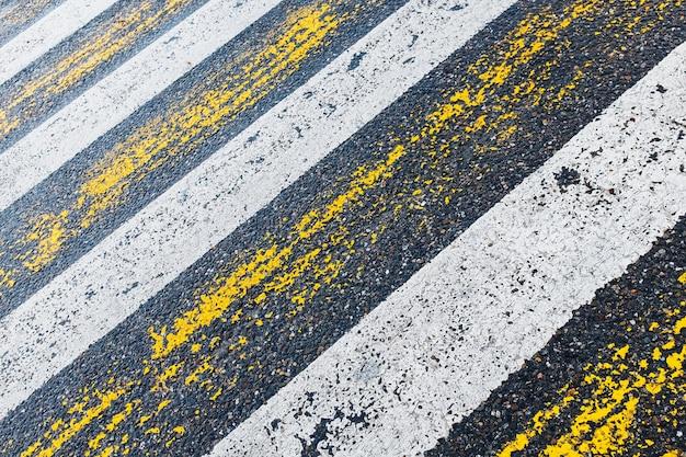 Przejście dla pieszych, żółte i białe paski na mokrym asfalcie w postaci faktury i podłoża
