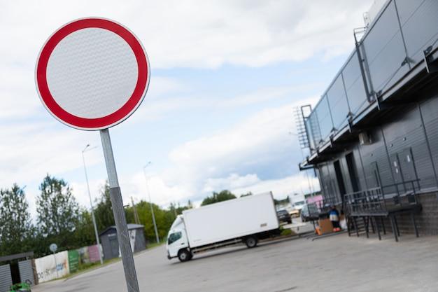 Przejście roadsign zabronione jest z tyłu sklepu z białą ciężarówką na wsporniku