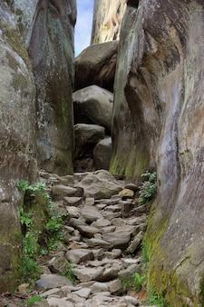 Przejście wąskim wąwozem między skałami w górach