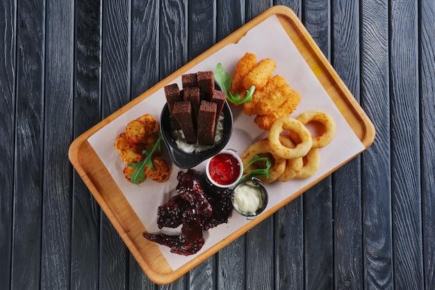 Przekąska do piwa. buffalo skrzydełka z kurczaka, frytkownice cebula, ziemniaki, bułeczki z grzankami, sos i ser