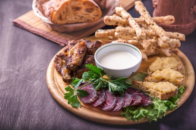 Przekąska do piwa z lato. smażone skrzydełka z kurczaka, kanapki z kawiorem gromadnikowym i paluszki chlebowe z sosem. smaczna przekąska
