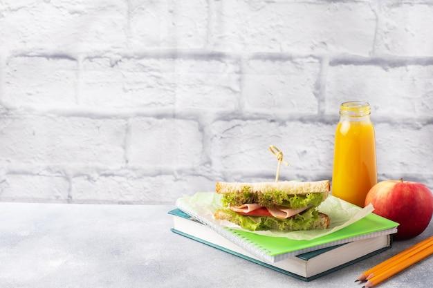 Przekąska do szkoły z kanapką, świeżym sokiem jabłkowym i pomarańczowym. kolorowe przybory szkolne, miejsce kopiowania,