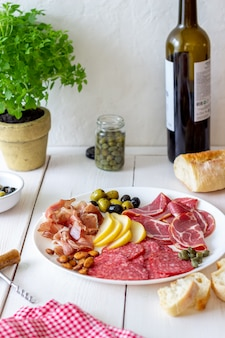 Przekąska do wina. prosciutto, szynka parmeńska, salami, migdały, oliwki, bagietka. antipasti