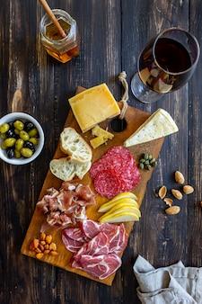 Przekąska do wina. prosciutto, szynka parmeńska, salami, migdały, oliwki, bagietka, ser pleśniowy, parmezan. antipasti