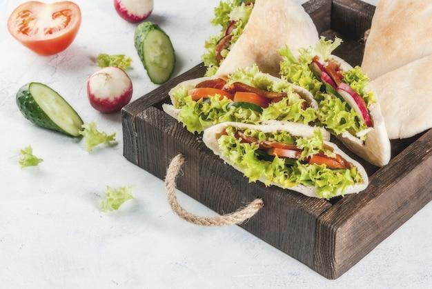 Przekąska. jedzenie na wynos, fast food na ulicy. kanapka pita z sałatką ze świeżych warzyw, ogórkiem, pomidorem, rzodkiewką, mięsem wołowym