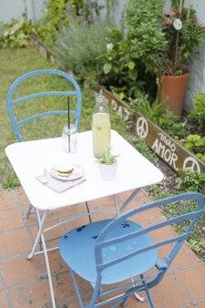 Przekąska, lemoniada i ciasto na stole w rustykalnym ogrodzie