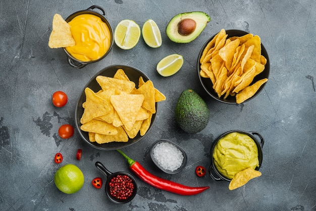 Przekąska na imprezę, frytki, nachos z sosami, na szarym stole, widok z góry lub na płasko