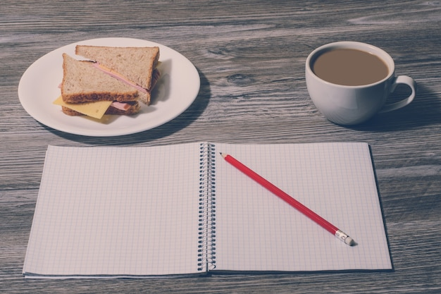Przekąska w pracy. smaczna kanapka z serem na talerzu, filiżanka gorącej kawy, otwarty notatnik z ołówkiem na szarym tle drewnianych. widok z góry, efekt vintage