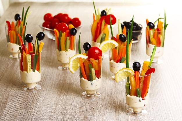 Przekąska warzyw w szklanych naczyniach na drewnie