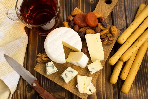 Przekąska z serów i paluszków chleba na brązowym tle drewniane widok z góry
