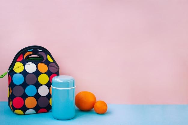 Przekąskę podczas przerwy w lunchbox. kolorowa torebka, niebieski termos, pomarańcza, mandarynka. różowy
