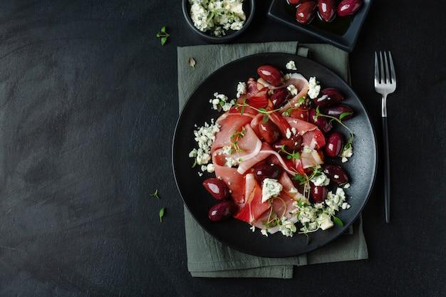 Przekąski antipasti na ciemnym talerzu z jamonem, oliwkami i serem pleśniowym. widok z góry.